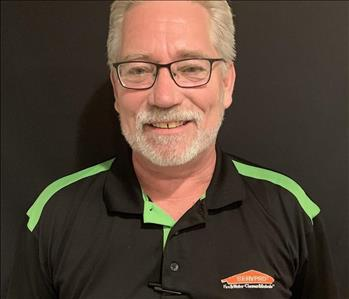 Male employee in black and green SERVPRO top, glasses white hair and beard