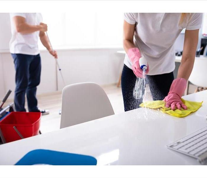 male spraying a white desk and wiping with a yellow rag in an office