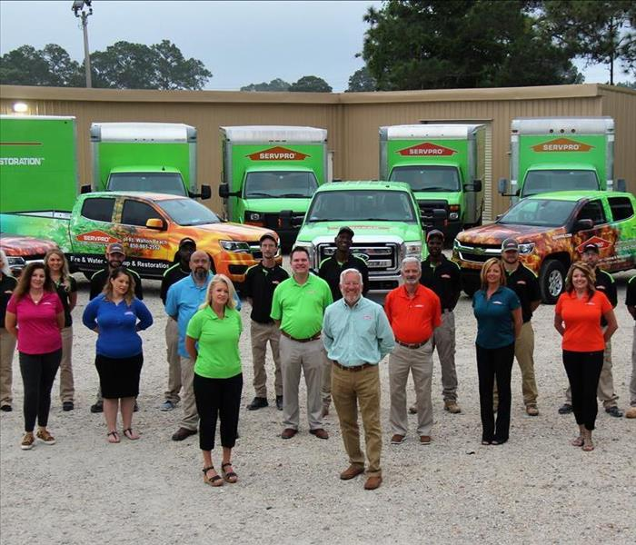 SERVPRO staff and crew photo in front of SERVPRO vehicles.