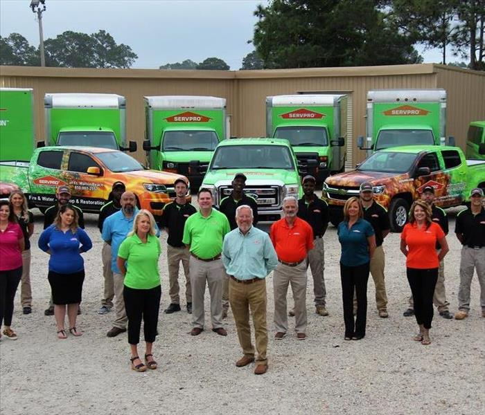 SERVPRO employees standing in front of vehicles.